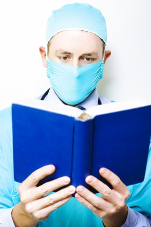 A masked male doctor stands concentrating on the reference book that he is reading and assimilating in a medical research and study concept photo