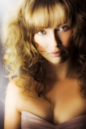 Romantic soft portrait of a beautiful busty fashion model with lovely wavy blonde hair curling down above a strapless dress Stock Photo - 14344095