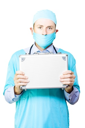 Conceptual image of a young male surgeon in a mask and gown holding up a small metal case signifying an organ donation or transplant Stock Photo - 14434653