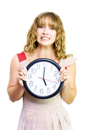 Attractive young blonde business woman clutches a clock showing the time as five oclock in a time to stop work conceptual of being out of time photo