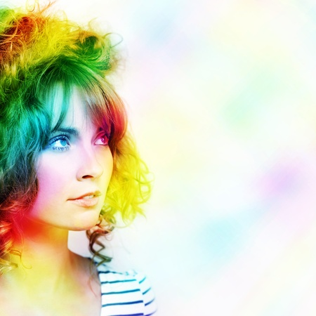 Colorful Abstract Design Of A Beautiful Young Woman With Colourful Wavy Hairstyle Standing In A Vibrant Rainbow Of Magic Colours With Space For Your Text photo
