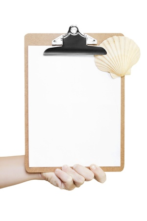 Male hand holding a clipboard with a single sheet of blank white paper and a fan-shaped seashell, conceptual of a summer vacation travel checklist photo