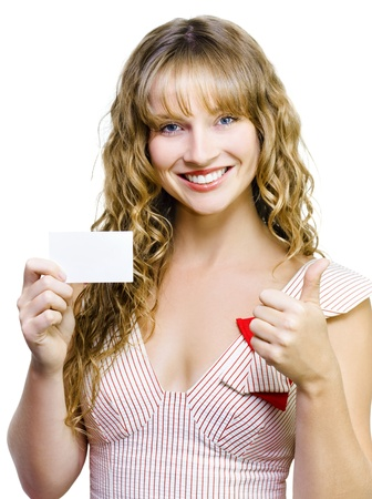 Upbeat beautiful woman with a lovely smile giving a thumbs up gesture while presenting her blank business card isolated on white photo