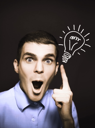 Shocked male business person pointing to light bulb illustration in a bright spark of ideas concept on dark copy space background illustration
