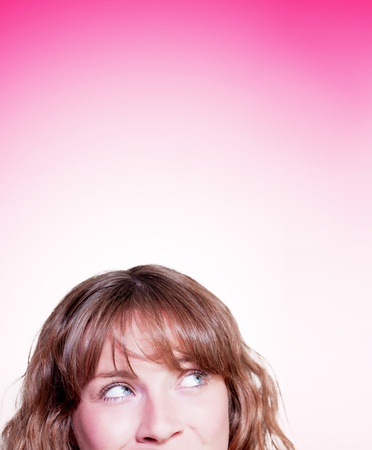 Portrait on the face of a beautiful young woman looking up onto blank copyspace in a room for text concept on pink background Stock Photo - 14796328