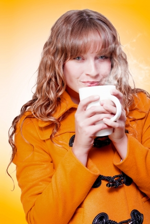 Woman in a warm winter coat sipping and savouring a mug of hot steaming coffee or soup which she is nurturing in cupped hands in a wintertime warm up conceptual Stock Photo - 17762512