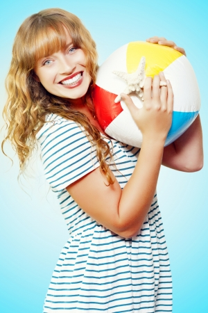 Excited smiling beautiful woman holding a plastic beachball and starfish conceptual of a tropical summer vacation against a turquoise blue background photo