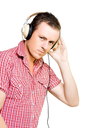 Young man with a serious expression in a red checked shirt wearing a pair of large wired circumaural headphones isolated on white photo