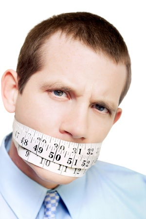 Man with tape measure around his mouth in a diet and weightloss concept isolated on white photo