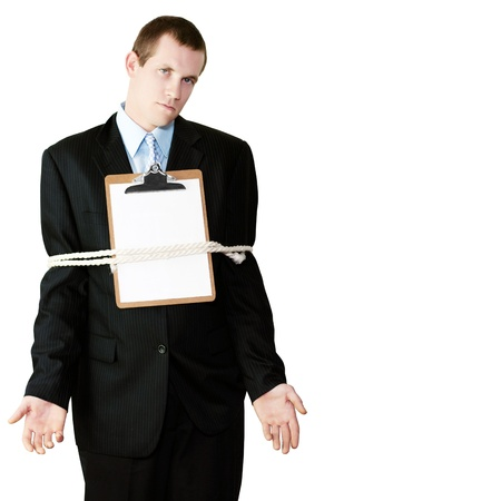 Handsome businessman standing with a clipboard with blank paper on his chest and his arms securely tied to his sides by a rope conceptual of being bound by the restrictive regulations of bureaucracy Stock Photo - 15260889