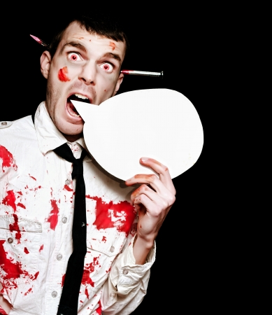 Comical Photo Of A Evil Halloween Zombie Shouting Out A Horror Message Of Blood And Gore Through A Round Speech Bubble On Black Background photo