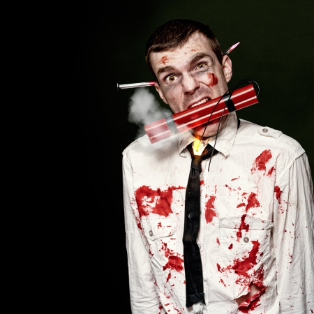 Zombie Suicide Bomber Holding A Mouthful Of Dynamite While Initiating A Halloween Zombie Apocalypse On Dark Studio Background  Stock Photo - 15408693