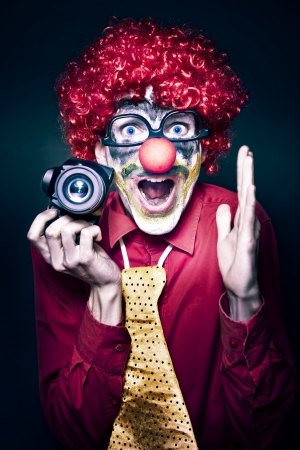 Excited Young Male Photographer Clown Holding Camera While Shouting Out Cheese At A Kids Birthday Party Celebration On Dark Studio Background photo
