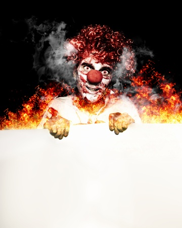 Retrato De Una Scary Creepy Clown Circus con un cartel en blanco copyspace mientras est� de pie en una llama de fuego en un concepto de Halloween Hot Specials photo