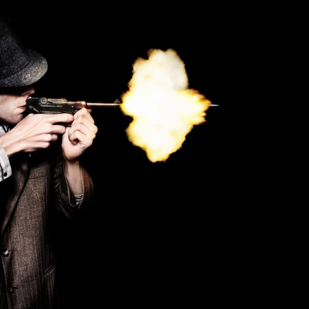Retro Male Gangster Shooting Old Fashioned Pistol On Black Background photo