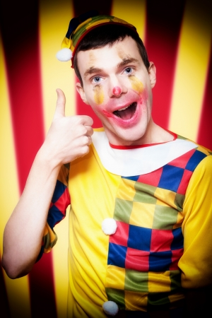 Playful Smiling Circus Clown Standing Inside Bigtop Tent Giving Thumbs Up For Good Entertainment While Gesturing A Trapeze Act Above Stock Photo - 15629714