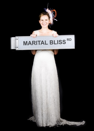 Happy Bride Holding Street Sign In A Concept Of The Saying On The Road To Marital Bliss photo