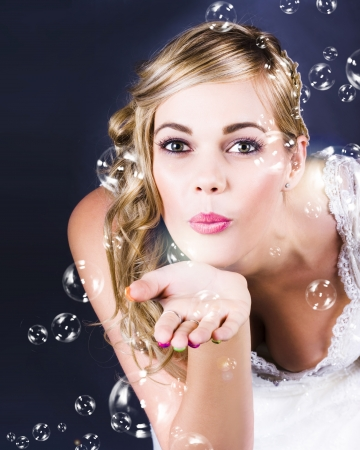 Beautiful Blond Bride Blowing Bubbles At Wedding Reception Celebration photo