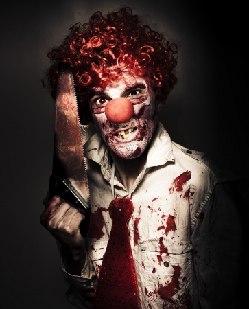 Frightening Portrait Of A Angry Carnival Clown Carrying Amputation Saw In Dark Slaughter House photo