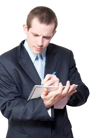 Smart young male personal assistant setting appointments in a handheld diary as he schedules meetings for his boss isolated on white background photo