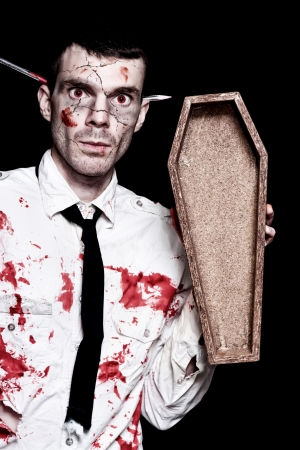 Halloween Businessman Covered In Blood Holding Open Funeral Casket On Black Background photo