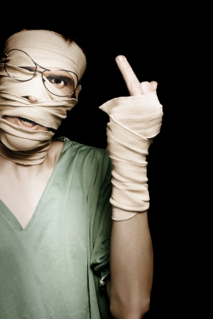 Person Wrapped In Bandages With Head Trauma Giving Rude Gesture In A Depiction Of A Impatient Medical Patient photo