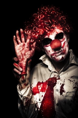 Horror Clown Waving Chopped Off Hand To Welcome You To A Evil Circus Act Of Terror On Black Background photo