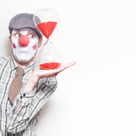 Funny Business Man In Clown Costume Holding An Egg Timer In A Running Out Of Time Concept On Copyspace photo