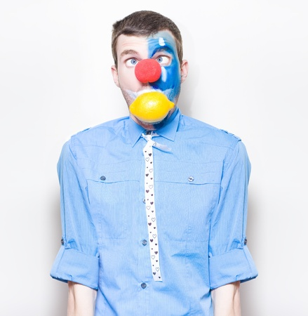 Funny Looking Clown Trying To Swallow A Lemon Whole With A Sour Expression In A Depiction Of Heartburn And Indigestion Stock Photo - 16128186