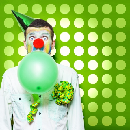 Excited Male Clown With Colourful Face Paint Blowing Up A Green Balloon While Having Fun Celebrating Kids Birthday Parties photo