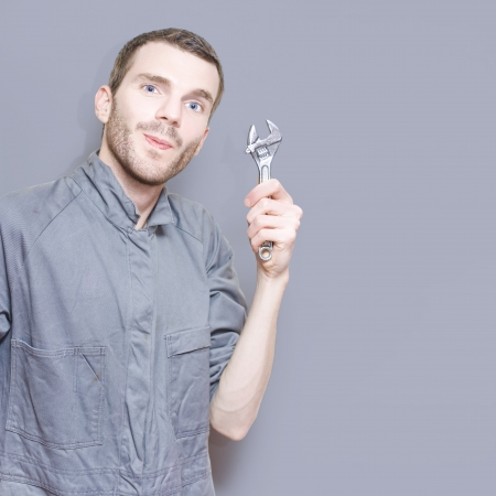 Smiling Young Male Mechanic In Boiler Suit Holding Wrench Against A Grey Copyspace Background photo