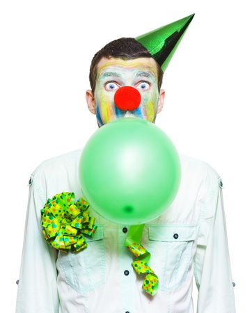 Isolated Birthday Clown In Party Costume, Looking Surprised.While Blowing Up Green Balloon Over White Background photo
