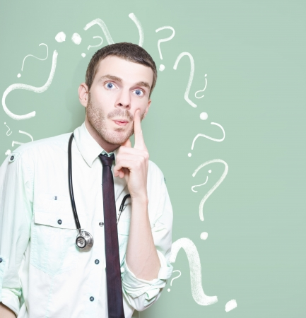 Confused Healthcare Doctor Standing Looking Puzzled Against A Green Question Mark Background In A Depiction Of A Unknown Cure Or Medical Mystery photo