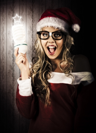 Smart Female Santa Claus Holding Fluorescent Xmas Tree Light Bulb With Star Top In A Depiction Of A Clever Christmas Gift Idea Stock Photo - 16639690