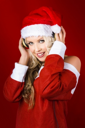Beautiful Young Woman Wearing Santa Claus Clothes Listening To Headphones On Red Christmas Background Stock Photo - 16639669