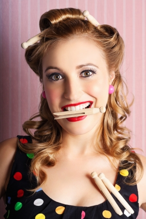 Funny Portrait Of A Happy Young Retro Woman Holding Clothes Pegs In Mouth When Doing Laundry Chores In A Pin-up Clothing Concept Stock Photo - 17160790