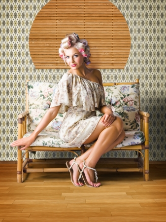 Sexy Fashion Photo Of Beautiful Girl Wearing Hair Rollers Sitting On A Vintage Floral Sofa In A Depiction Of Pinup Style Glamur photo