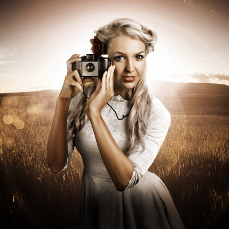 Pretty Retro Girl Taking Landscape Picture Using Vintage Film Camera photo