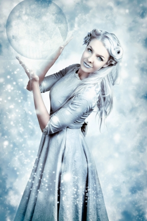 Magic Winter Girl Wearing Luxury Fashion And Elegant Hairstyle With Beautiful Make-up Holding Crystal Ball In Falling Snow photo