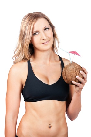 Beautiful blonde woman in black bikini on a tropical vacation holding a fresh coconut fruit cocktail husk celebrating a luxury holiday in the sun photo
