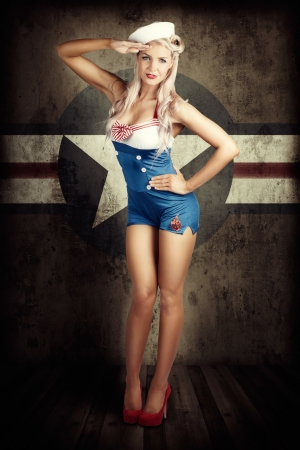 Grunge Portrait Of A Beautiful American Retro Female Cadet Dressed In Navy Uniform While Saluting In A Military Pin Up Girl Concept On Army Star Background photo