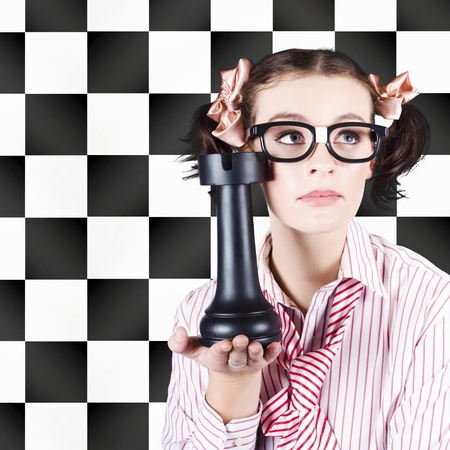 A pretty brainy nerdy young woman in glasses holds an outsize chess piece in her hand against a black and white chessboard backdrop advocating intelligent marketing with prior planning and strategy photo
