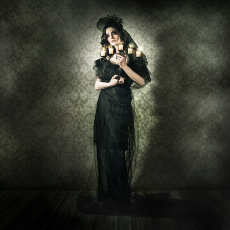 Dramatic Dark Portrait Of A Beautiful Gothic Model Posing Inside Vintage Haunted House In A Depiction Of Alternative Fashion photo