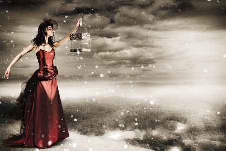 Beautiful Winter Fashion Woman In Creative Makeup Holding Open Bird Cage On Mountain Landscape In A Depiction Of Freedom photo