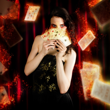 Creative Fine Art Photo Of A Beautiful Mystic Magician Holding Flaming Cards In A Depiction Of Tarot Fortune Telling photo