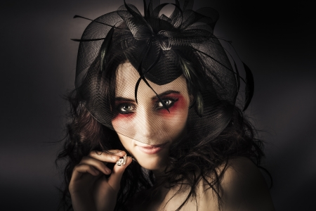 Dark Fashion Portrait Of A Beautiful Elegant Lady In Luxury Fascinator And Jewellery Necklace photo