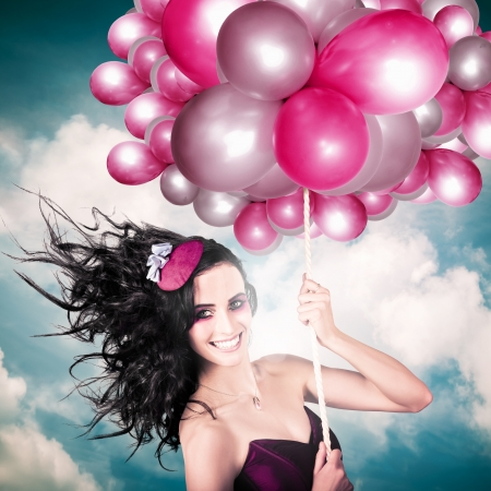 Beautiful Smiling Australian Girl Flying High Wearing Headpiece With Balloons In A Depiction Of The Fashion Of The Field During The Melbourne Cup Spring Carnival Horse Racing Festival photo