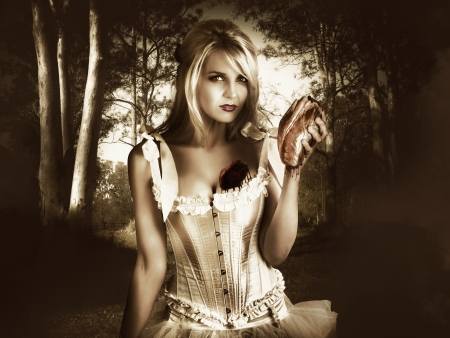 Dramatic Portrait Of An Emotional Blond Woman Standing In A Dark Forest Holding Her Own Bleeding Heart After Ripping It Out Of Her Chest, In A Separation From Love Conceptual Stock Photo - 17860702