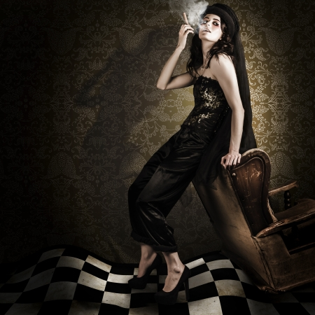 Artistic Fashion Photo Of Beautiful Avant-garde Woman Smoking Cigar In A Dim Vintage Interior While Portraying The Twisted And Edgy Look Of Grunge Fashion photo