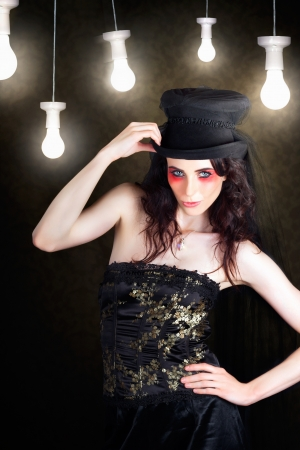 Dark Headdress Fashion Portrait Of A Female Beauty Posing Under Hanging Light Bulbs Wearing Top Hat Headgear In A Depiction Of Bright Headwear Ideas Stock Photo - 17889063